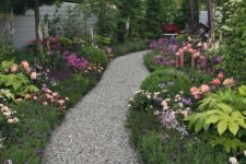 a gravel pathway lined by lush greenery and blooms looks like a path ina  magical forest