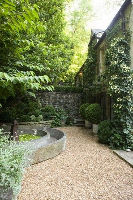 neutral-colored gravel combined with concrete and stone plus lush potted greeenery for amodern garden