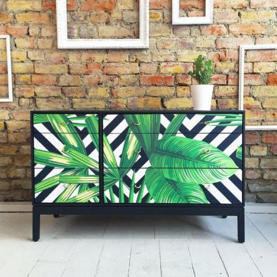 a black dresser with drawers covered with bright tropical leaf contact paper looks very contrasting