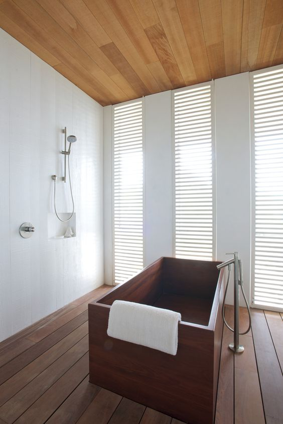 a contemporary bathroom with a rich-stained wooden rectangular bathtub for maximal relaxation