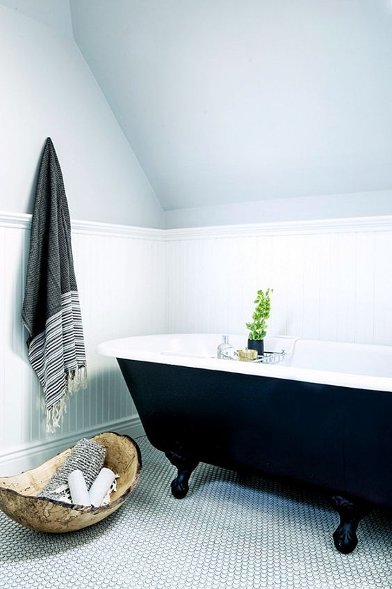 you can make a statement in a neutral or monochromatic bathroom with a black clawfoot tub