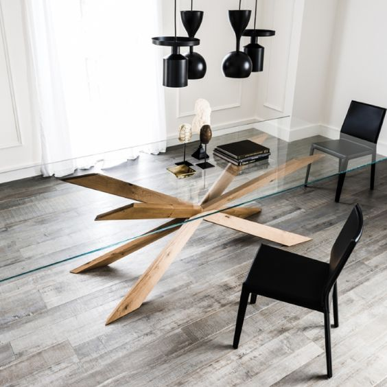a chic dining table with a large glass tabletop and creatively place legs of solid wood looks wow