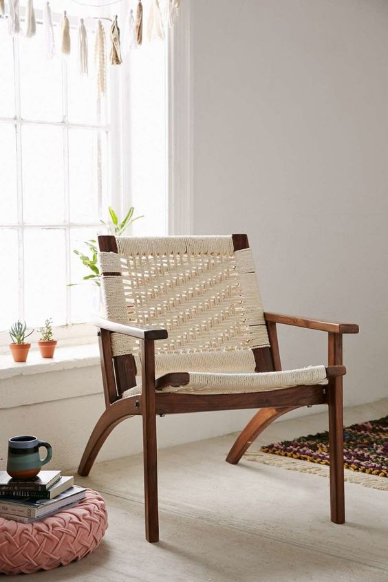 a chic mid century modern chair with a rich stained base and white macrame for a boho feel