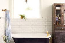 03 a midnight blue clawfoot bathtub wth gilded legs and matching fixtures plus a Moroccan lamp for a chic space