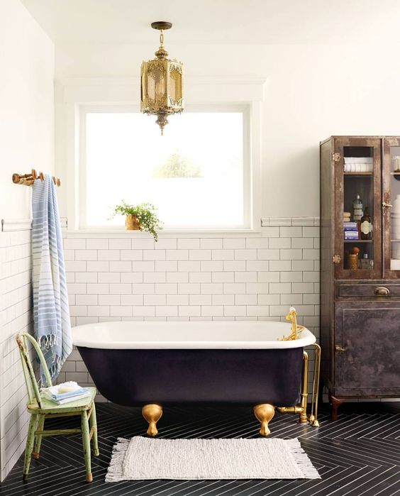 a midnight blue clawfoot bathtub wth gilded legs and matching fixtures plus a Moroccan lamp for a chic space