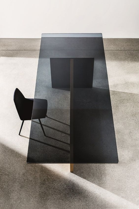 a chic smoked glass dining table with a comfy wooden base is ideal fro a minimalist dining room
