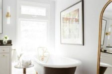 05 a black clawfoot bathtub and black fishcale tiles on the floor are a chic combo for a refined bathroom