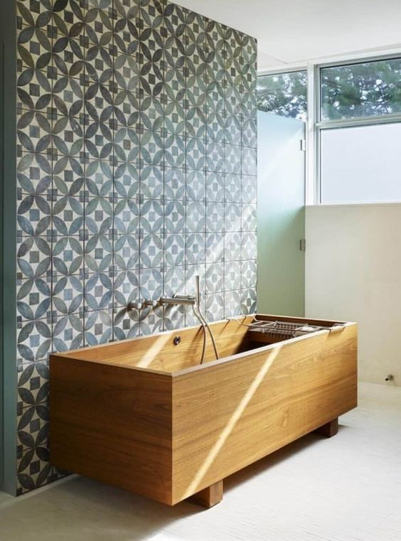 a rectangular wooden bathtub on legs looks contrasting with a blue mosaic wall in foront of it