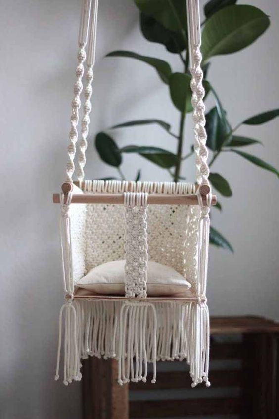 a macrame baby chair with long fringe and some wooden sticks is a very cute idea