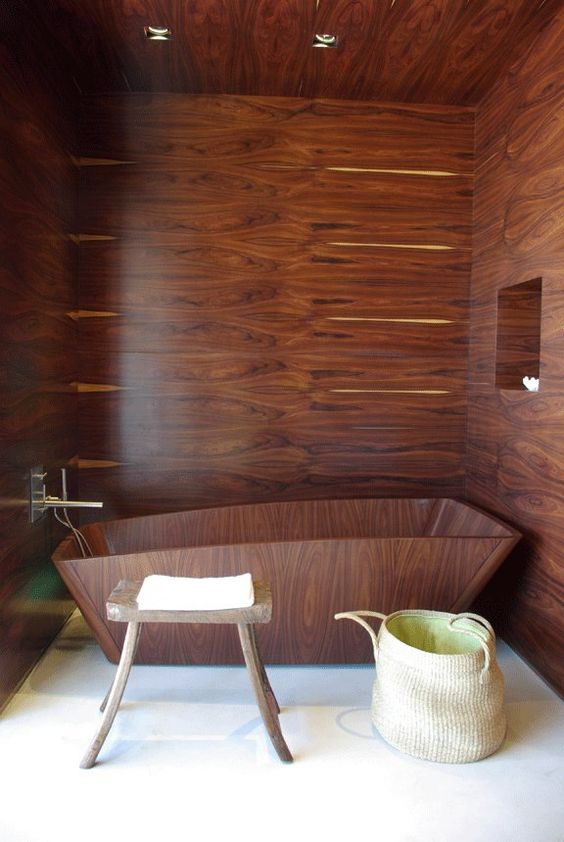 a sculptural wooden bathtub and matching walls for a moody and relaxing bathing nook