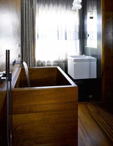 a contemporary rectangular wooden bathtub in a minimalist bathroom with curtains for privacy