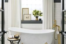 07 a marble clawfoot bathtub with gilded legs and matching faucets is a gorgeous and sophiticated option
