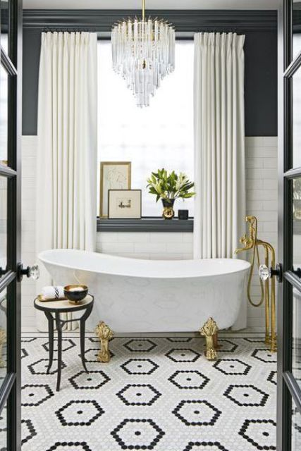 a marble clawfoot bathtub with gilded legs and matching faucets is a gorgeous and sophiticated option