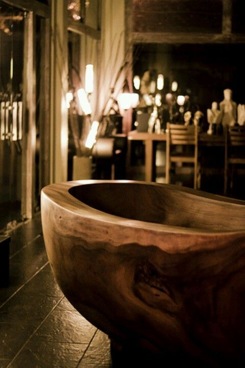 a carved wooden bathtub with natural grain will turn your bathroom into a natural relaxation oasis