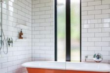 08 a monochromatic bathroom wiht a bold orange clawfoot bathtub to add a touch of color and interest