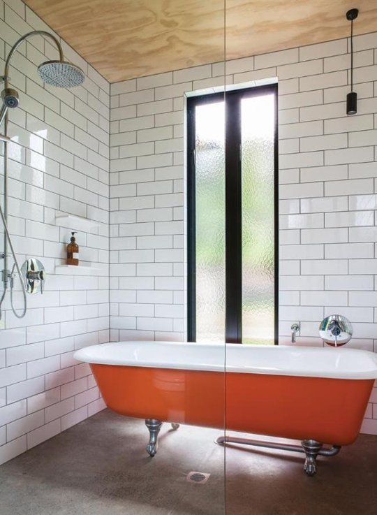 a monochromatic bathroom wiht a bold orange clawfoot bathtub to add a touch of color and interest