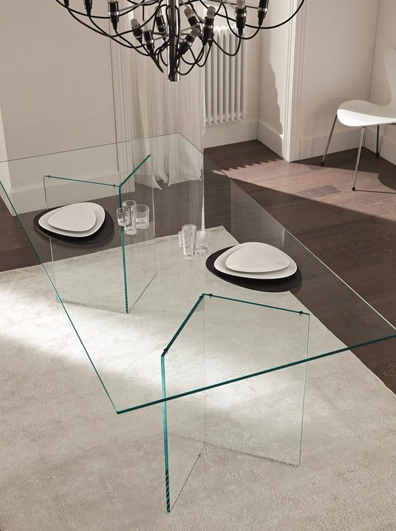 a minimalist dining table with geometric glass legs and a glass tabletop seems to be floating in the air