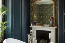 09 a moody Victorian bathroom with a sophisticated clawfoot bathtub and a large crystal chandelier