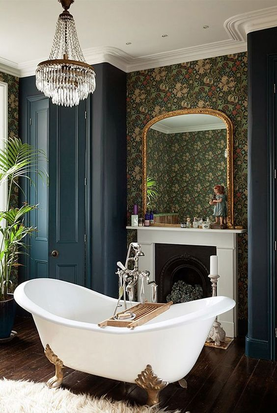a moody Victorian bathroom with a sophisticated clawfoot bathtub and a large crystal chandelier
