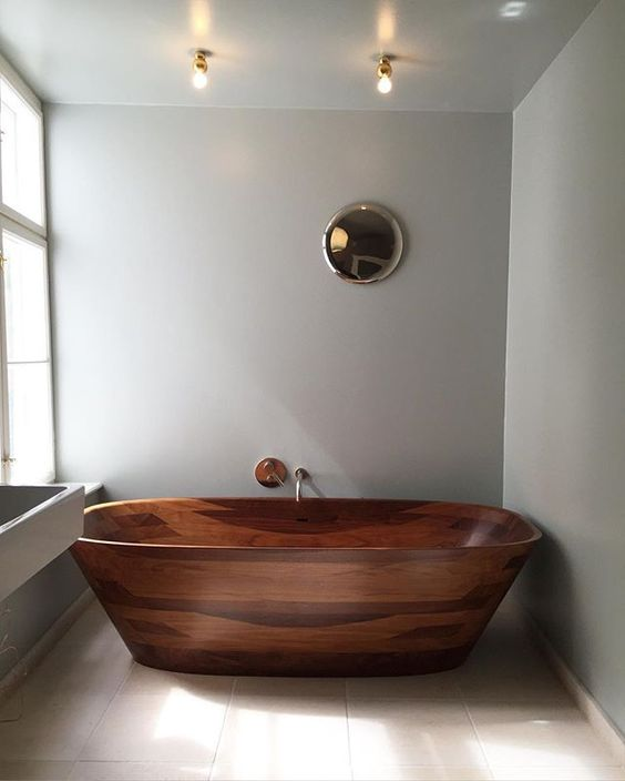 a large rich-stained wooden bathtub with gold fixtures makes a colorful statement in a neutral bathroom