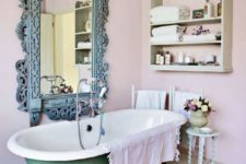 10 a pastel eclectic bathroom in pink and mint with a patina mirror and a green clawfoot bathtb