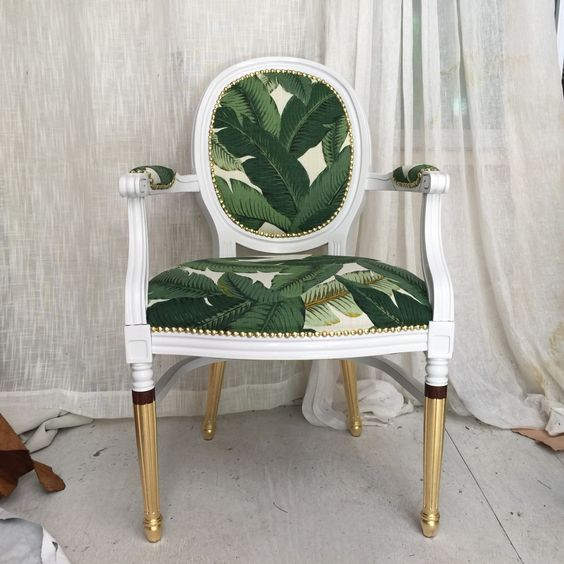 a vintage and super elegant chair with tropical leaf upholstery and gilded legs is a very chic idea