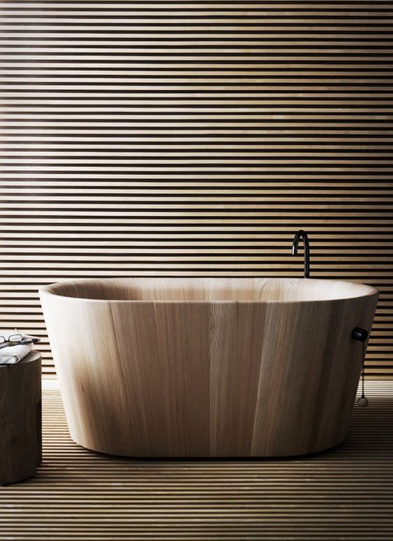 a polished free-standing wooden bathtub in a bathroom clad with wooden planks for a minimalist and natural space