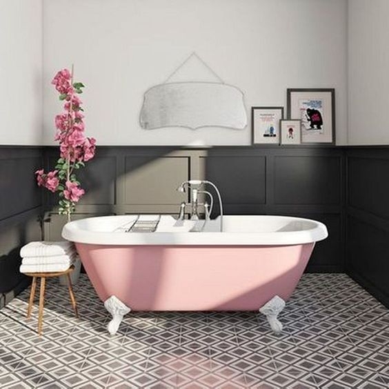 an elegant monochromatic bathroom with a pink clawfoot bathtub that adds a girlish touch to the space