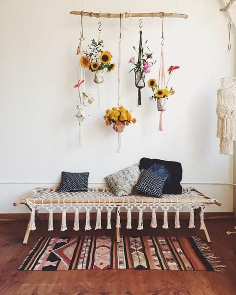 a macrame daybed with tassels and macrame pot hangings are perfect for a boho space