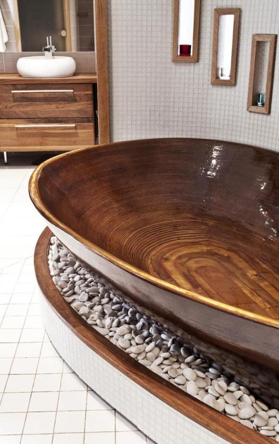 a relaxing polished wood bathtub placed on a platform with pebbles brings ultimate relaxation