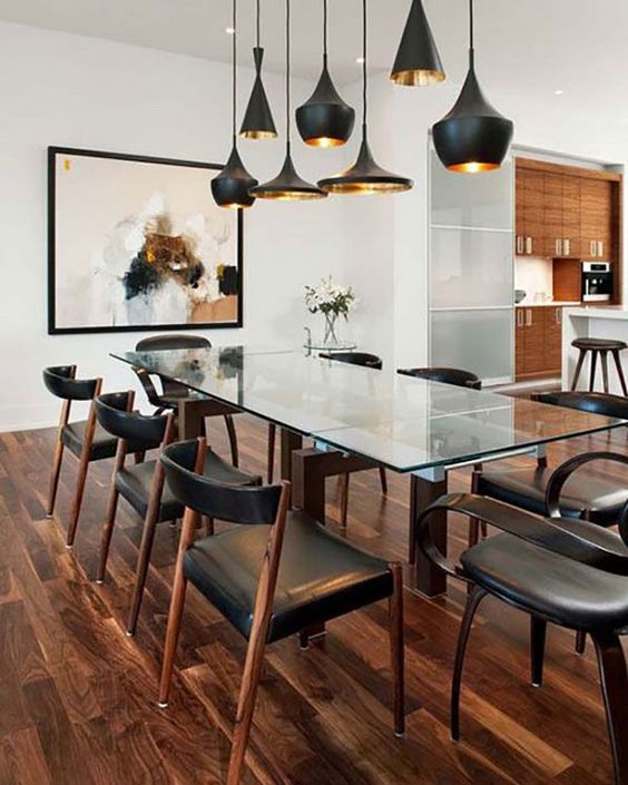 a stunning dining table with dark stained legs and a glass tabletop is complemented with dark chairs