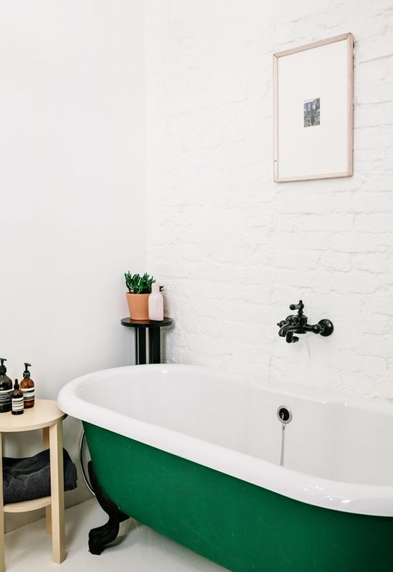 an emerald clawfoot bathtub with black legs is a bold colorful touch in a neutral bathroom