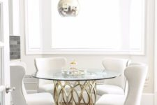 14 a chic dining table with a catchy metal base and a round glass tabletop accented with pendant lamps