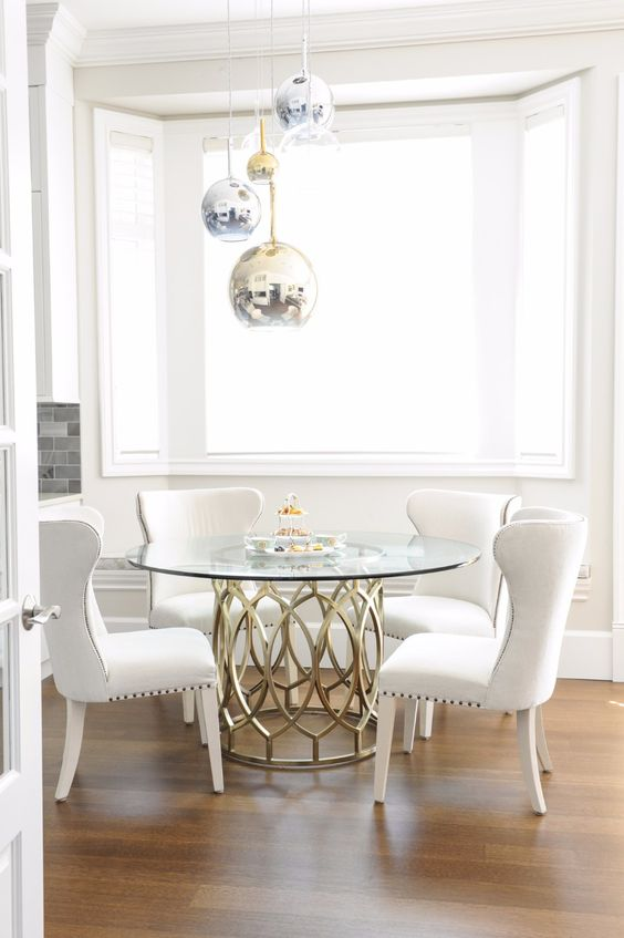 a chic dining table with a catchy metal base and a round glass tabletop accented with pendant lamps