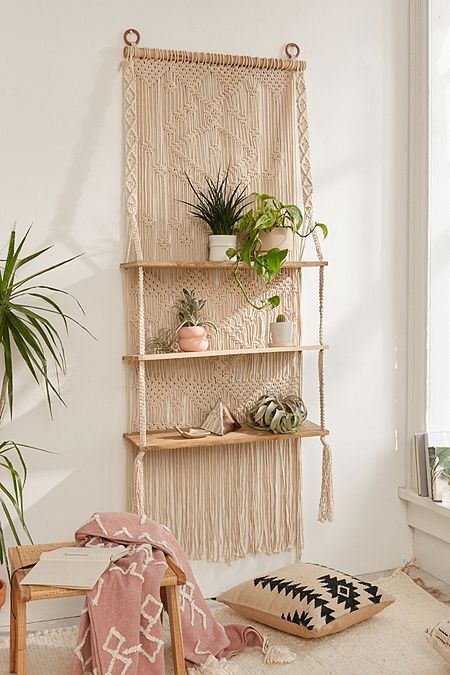 a macrame hanging shelf includes a hanging and shelves themselves plus soem long fringe