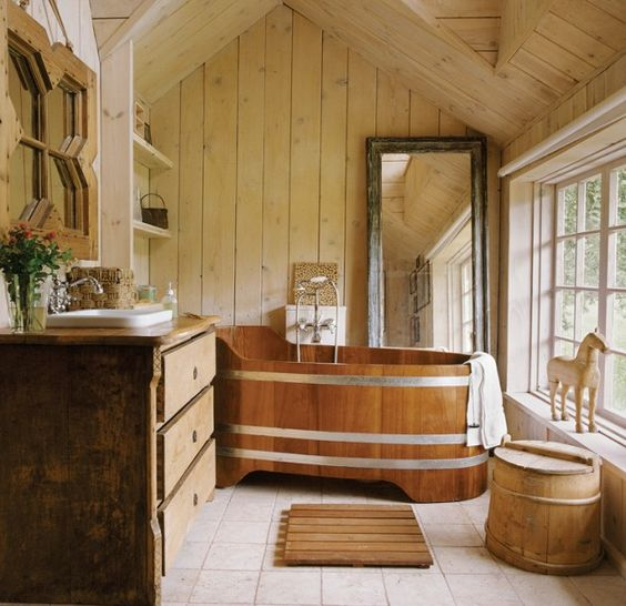 a wood and metal bathtub easily fits a rustic bathroom with tiles on the floor, wooden walls and a wooden vanity
