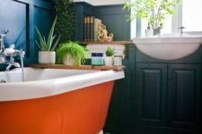 14 an orange clawfoot bathtub with white legs adds a colorful touch to the moody space