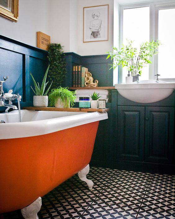 an orange clawfoot bathtub with white legs adds a colorful touch to the moody space
