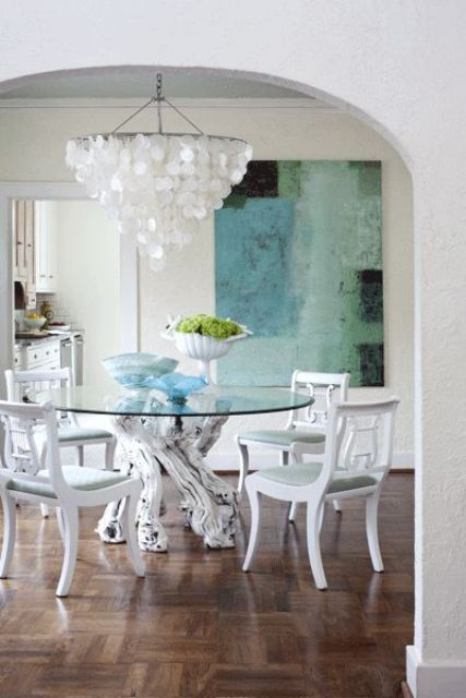 a creative dining table with a round blue glass tabletop and whitewashed driftwood to hold it