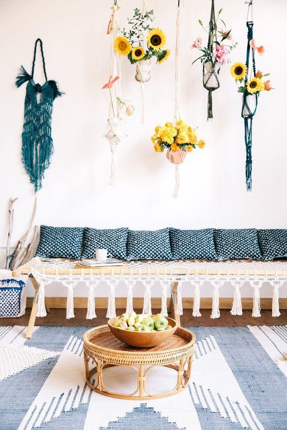 a modern macrame daybed with tassels, blue printed pillows and colorful macrame hangings for planters