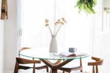 16 a gorgeous glass dining table with a catchy wooden base and a round glass tabletop for a mid-century modern room