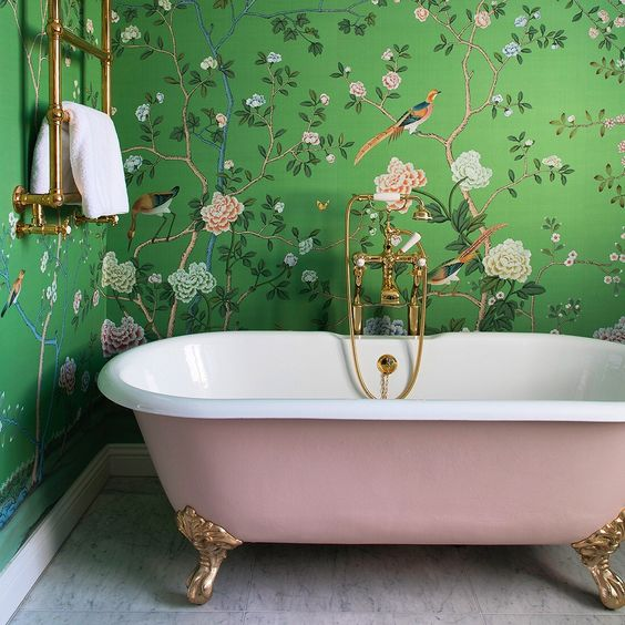 floral wallpaper and a pink clawfoot tub that matches the patterns create a chic and refined space