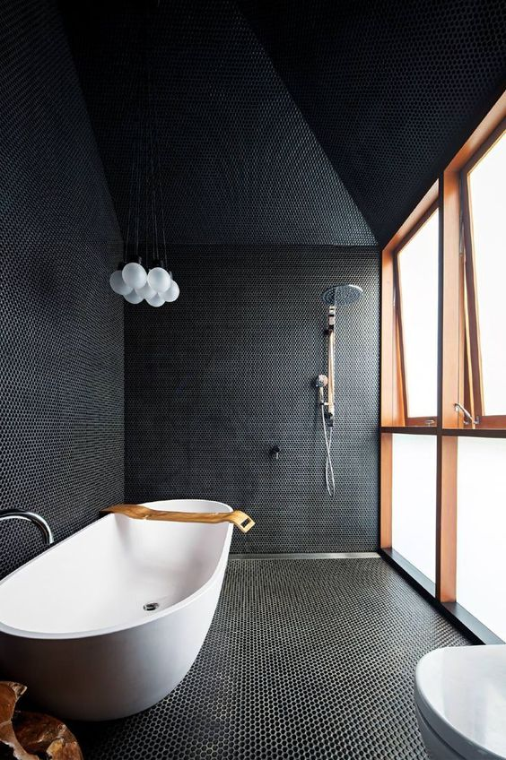 a black bathroom fully clad with penny tiles with white grout, with a frosted glass wall and a free standing bathtub