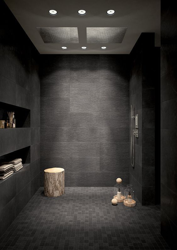 a black bathroom with large and smaller scale tiles, built-in shelves and a tree stump table