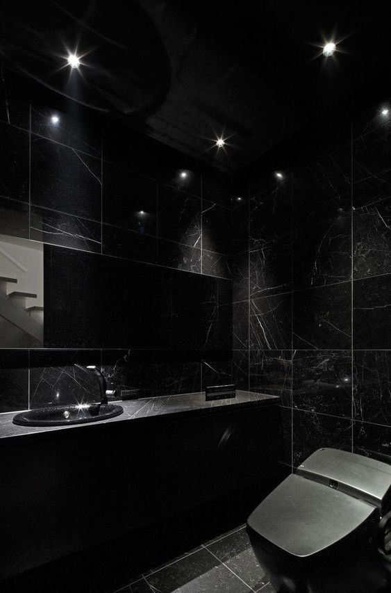 a chic black bathroom with blakc marble tiles and a blakc marble vanity plus a black toilet