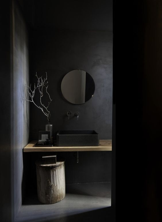 a chic minimalist black bathroom with a matte black sink and walls plus some light-stained touches