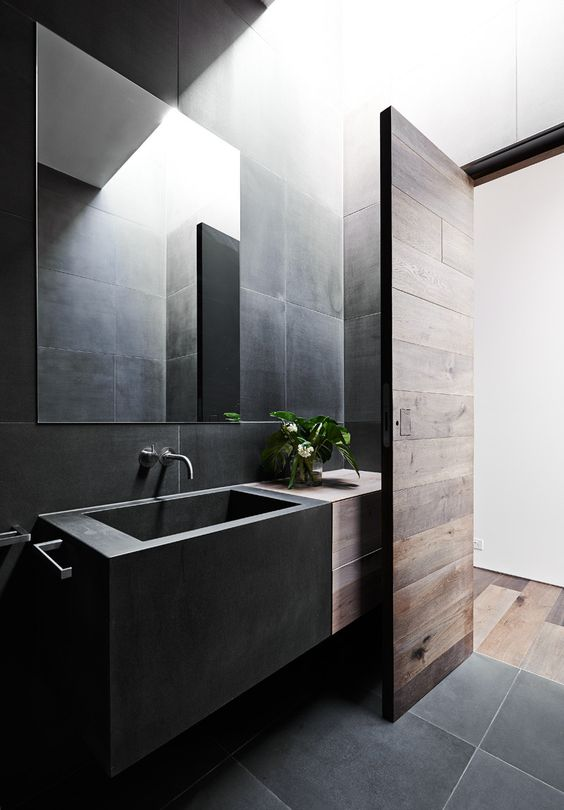 a contemporary black bathroom done with large scale tiles, a box matte black sink and some rich-stained wood