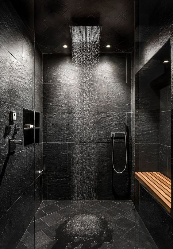 a contemporary black bathroom done with textural black tiles, a rain shower and a wooden bench