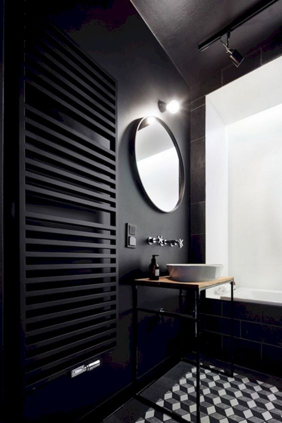 a contemporary black bathroom with matte black walls and a radiator, black tiles and a graphic tile floor