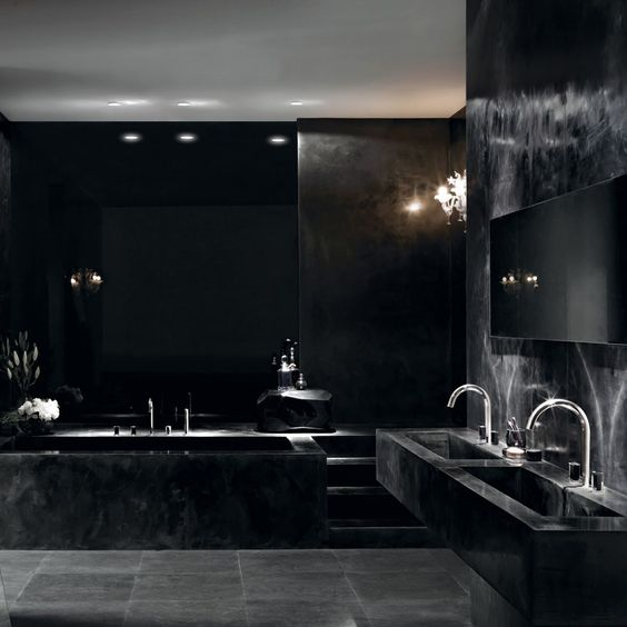 a luxurious all-black bathroom with a marle tub and sinksand touches of shiny metal